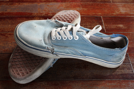 Old blue canvas shoe on wooden floor. photo