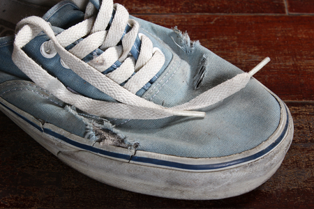Old blue canvas shoe on wooden floor. Stock Photo