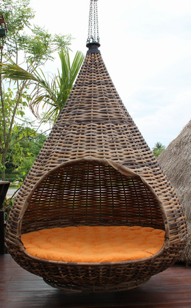 Hanging brown rattan chair with a large orange seat. photo