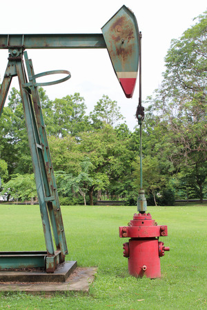 oil park: Old oil nodding donkey pumpjack in the park. Stock Photo