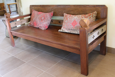 Teakwood bench with pillows on floor. photo