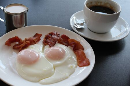 sunnyside: Continental breakfast of sunnyside up eggs, bacon and coffee.