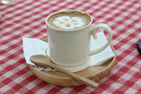 Hot cappuccino in white cup on pink tablecloth. photo