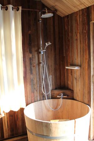 ensuite: Shower with vertically adjustable shower tap and wooden bathtub in bathroom wooden design.
