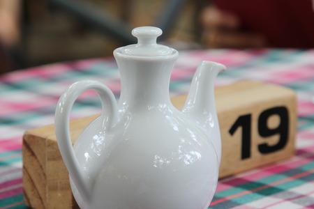 wooden stick: Ceramic tea pitcher and wooden stick.