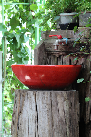 to sink: Red sink with faucet on the stump.