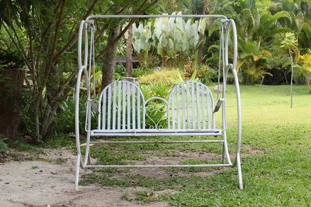 swing seat: White garden swing seat alone in the garden.