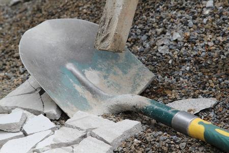 Old shovel lain on the gray gravel.