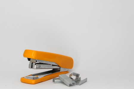 joins: Closeup of orange stapler and staple.