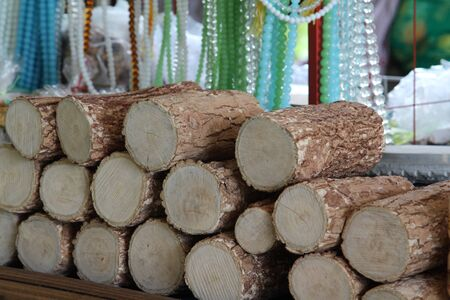 face in tree bark: Pile of tanaka in market, cosmetics Myanmar.