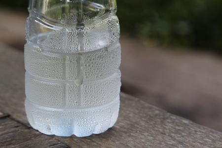 condensacion: Botella de plástico de agua fría con gotas de condensado. Foto de archivo
