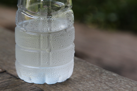 Plastic bottle of cold water with condensate drops.