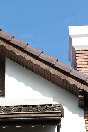 gable house: Gable of a white house with brown roof tiles.