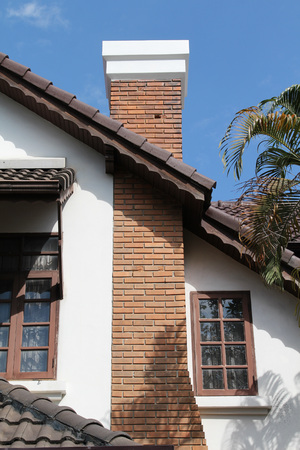 house gable: Gable of a white house with brick-made chimney. Stock Photo