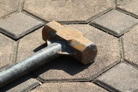 slovenly: Rusty sledge hammer on concrete block floor.