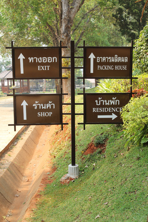 sign post: Brown sign post in Thai and English.