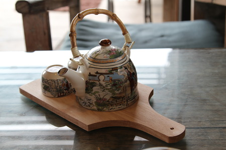 chinese tea pot: Chinese tea pot with two small tea cup on wooden saucer.
