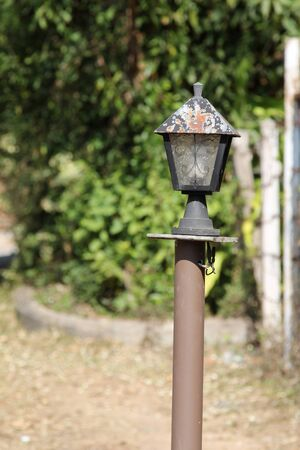 lamp post: Traditional old garden lamp on brown post. Stock Photo