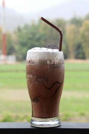 Iced cocoa with whipped cream and oreo biscuit topped. Stock Photo
