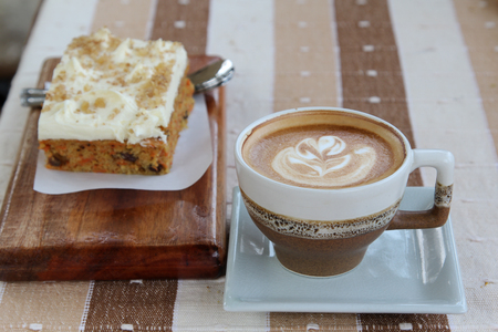 A cup of hot cappuccino with cake on table. Stock Photo