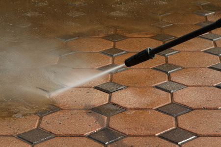 Cleaning concrete block floor by high pressure water jet. Stock Photo