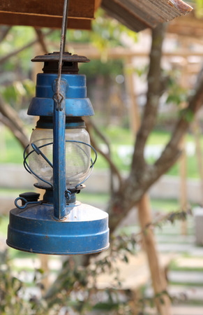 dowdy: Old blue oil lamp hanging on wooden bar.