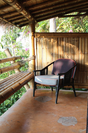 seating area: Outdoor patio seating area in bamboo house with brown rattan chair.