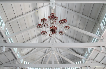 Chandelier on white roofing structure.