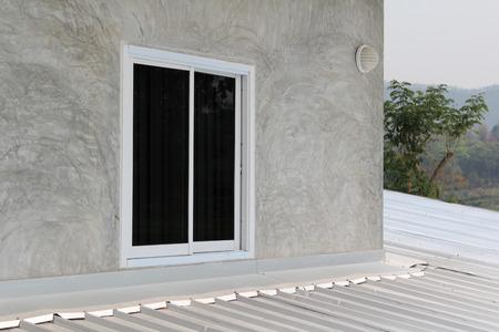 Aluminum sliding window on gray concrete wall. Stock Photo