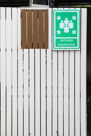 assembly point: Assembly Point Sign on white wooden wall. Stock Photo