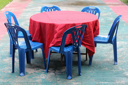 round chairs: Round table covered with red tablecloth and blue plastic chairs. Stock Photo
