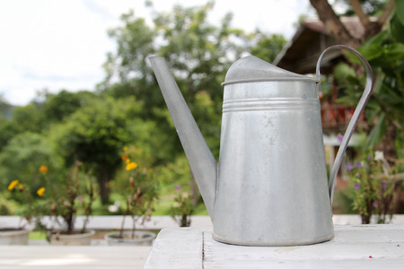 galvanized: Zinc watering can on wooden chair for decoration garden. Stock Photo