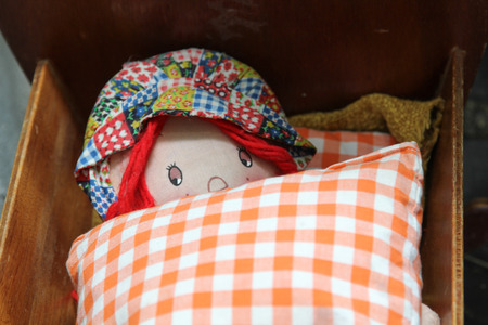 wooden bed: Girl doll sleeping in a wooden bed.