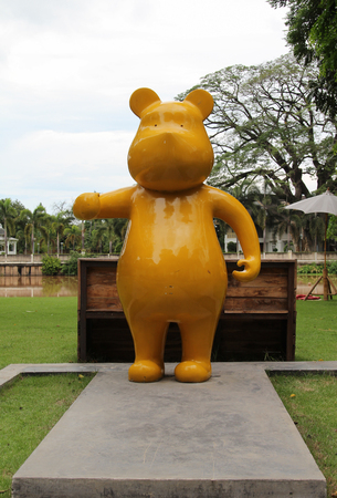 fibra de vidrio: Estatua amarilla del oso grande que se coloca en piso concreto. Foto de archivo
