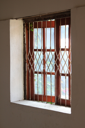 window grill: Old style Thai window on concrete wall. Stock Photo