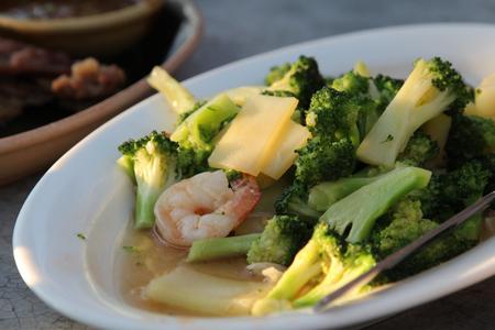 Thai food, stir-fried broccoli with shrimp on white plate.