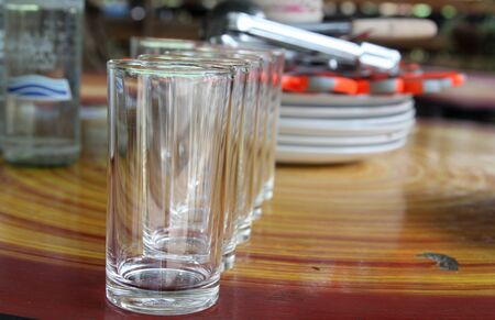Row of empty water glass on wooden table.