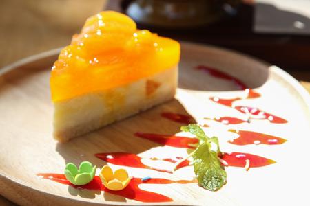 Orange cake on wooden plate, focus on small flower.