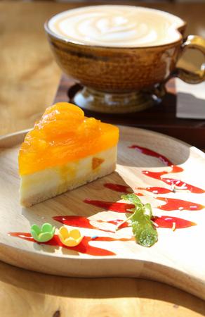 Orange cake on wooden plate.