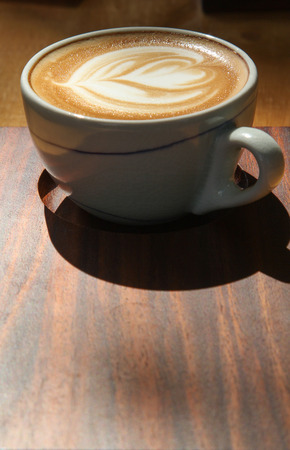 A cup of hot cappuccino on table. Stock Photo
