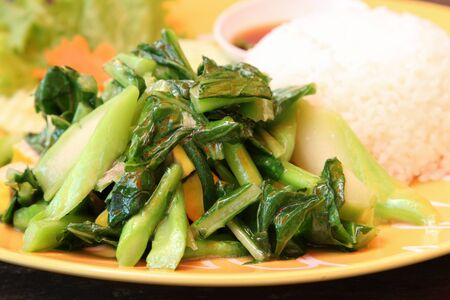 Thai food, stir-fried kale with rice on yellow plate.