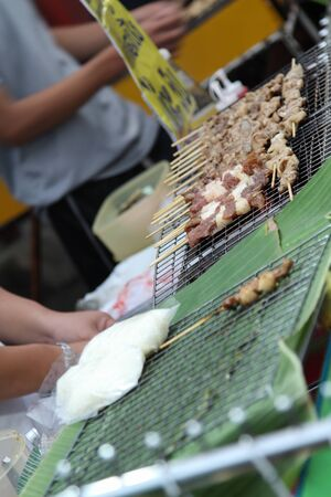 Thai food, traditional grilled pork on stove at market.