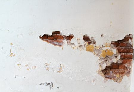 Old damaged stucco wall with original brick.