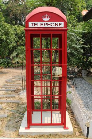 Red vintage telephone booth in the garden. Stockfoto