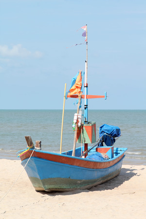 The wooden fishing boat on the beach. Stock Photo