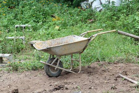Old yellow wheelbarrow in construction site.