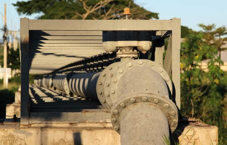 Large gray steel plumbing pipe on pipe-bridge.