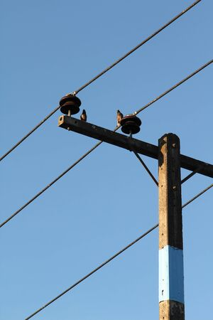 Electrical pole with blue sky background.