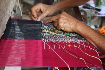 Woman hand weaving traditional Thai cloth at Mae Chaem, Chiangmai, Thailand.