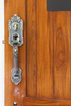 Antique style door handle on wooden door.